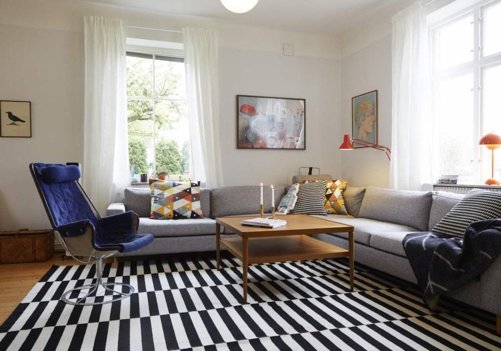 Hörnsoffan från Bolia.com får färg av Cecilias egenhändigt sydda kuddfodral. Den blå Jetson-fåtöljen kommer från Filips föräldrar och mattan är populära Ikeaklassikern Stockholm.