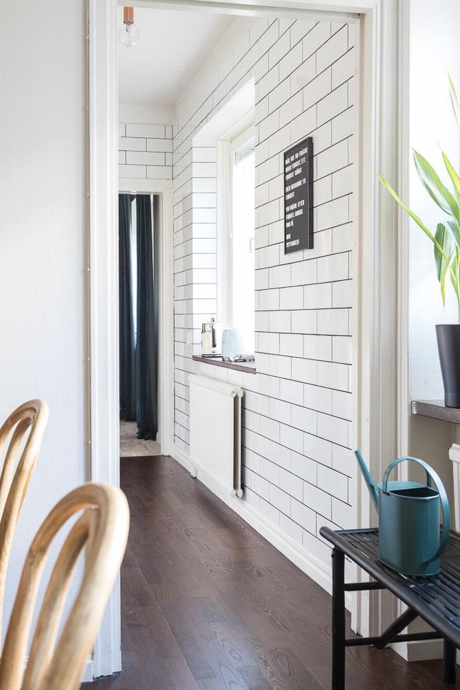 Alla väggarna i köket är kaklade ända upp till taket med vitt kakel och svart fog.