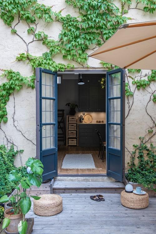 Vackra dubbeldörrar i fransk stil leder till uteplatsen och innergården vilket ger villakänsla mitt i Stockholm. Paret har låtit återskapa de djupa dörr- och fönsterfodren i sekelskiftesstil. Golvmatta från Tell me more.