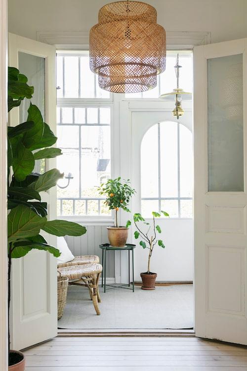 Sekelskiftesvillan är fylld av snickarglädje och ljusinsläpp inramat av vackra fönster. Bottenvåningens glasveranda är ett skönt rum för avkoppling. Taklampa från Ikea, liksom bord och stolar.