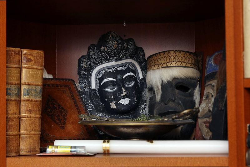 Hyllorna är fyllda av reseminnen, som dessa masker från Indonesien, Mexiko och Kina.