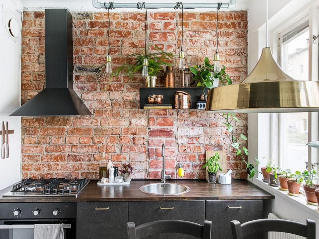 Tegelväggarna och glasväggen ger lägenheten en industrikänsla.