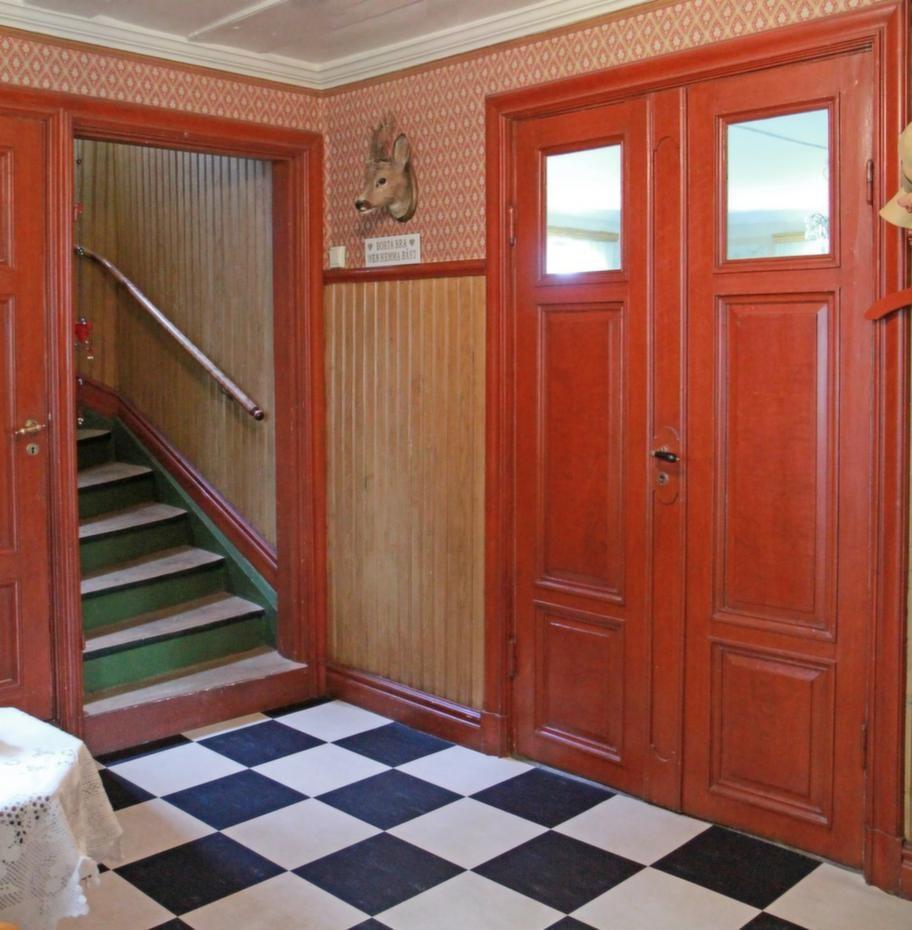Rött &amp; rutigt<br>Trappan till övervåningen i den välkomnande hallen. Alla snickerier är fernissade i gammal stil och golvet är schackrutigt. Den svart- och vitrutiga mattan är nyinlagd.