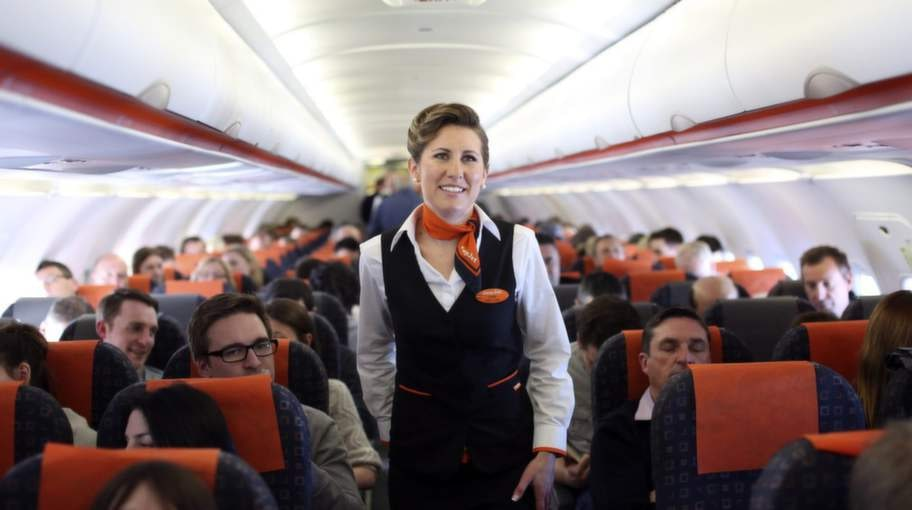 an easyjet plc flight attendant walks down the aisle of the aircraft during the company's inaugural flight from gatwick airport in the u.k., to domodedovo airport in moscow, on monday, march 18, 2013. easyjet plc's inaugural flight to moscow today will see the u.k. discount carrier go head-to-head with british airways as it targets a bigger share of europe's lucrative business-travel market. photographer: chris ratcliffe/bloomberg via getty images   publicerad text:  publicerad bildtext:värdefull. flygvärdinnor vet värdet av att en uniform inte bara ger en hygienisk fördel, utan att den också hjälper de anställda att upprätthålla professionell distans och disciplin. foto: getty images