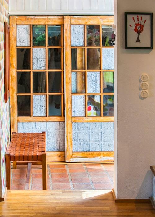 Gamla matkällaren har blivit en varm och ombonad entré in i huset. Garderoben ryms bakom två skjutdörrar som Peter har byggt av gamla fönsterpartier. På de ställen där rutor saknades sattes tunn, mönstrad plåt in.