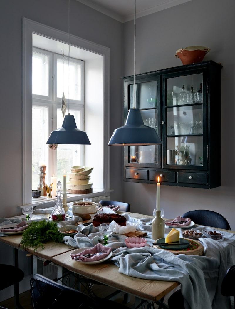 I köket står ett gammalt bord från Sverige, de blå lamporna hittade Maj i en container med saker som skulle slängas. Vitrinskåpet är fyllt med fynd från loppmarknader och resor.