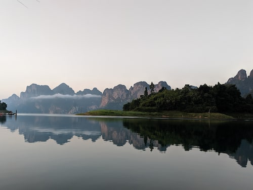 Morgondimma över en spegelblank sjö.