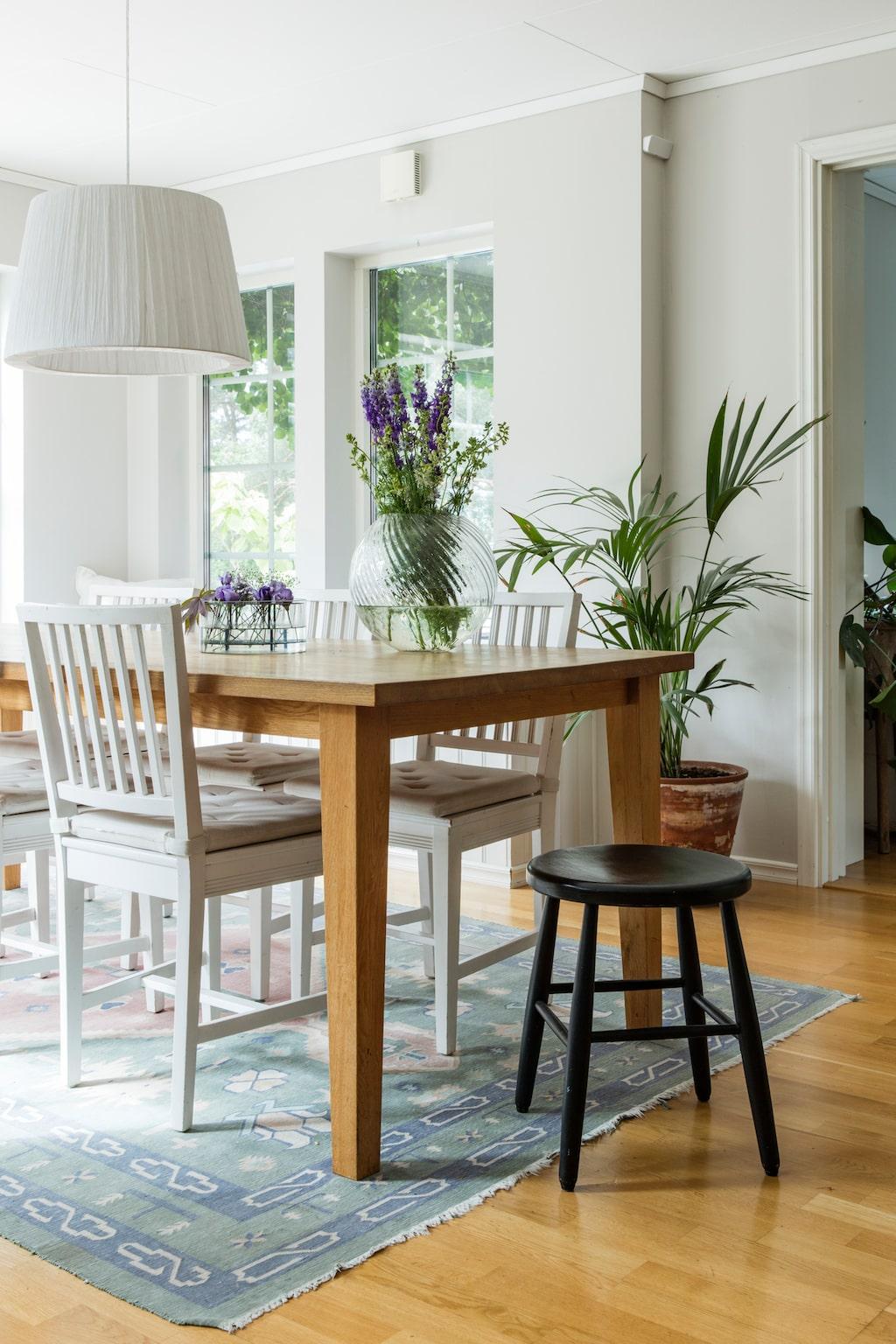 På den ljusa matplatsen med utsikt över trädgården och sluttningen står ett bord från Room, stolar från Allinwood och pall från loppis. Mattan är en indisk dhurrie.