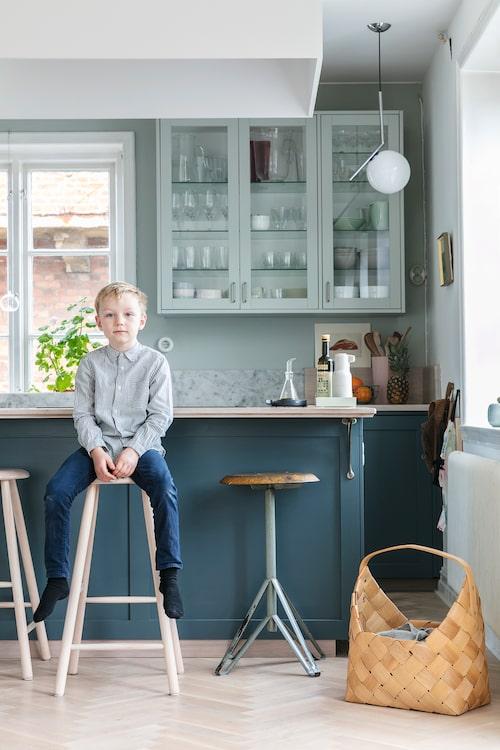 Stig trivs i köket på bottenplan som har öppen planlösning med kök, matplats och vardagsrum i ett. Att köket skulle ha en mörkare kulör på bänkskåpen och en ljusare på väggskåpen stod överst på önskelistan. Det ljusa trägolvet lades in tidigare – bottenvåningen hade tidigare samma mörkbetsade golv som ovanvåningen. Köket är byggt av Ikea-stommar som fått luckor från Picky Living, och sedan målats. Pallarna vid köksön, från museishopen på Louisiana.