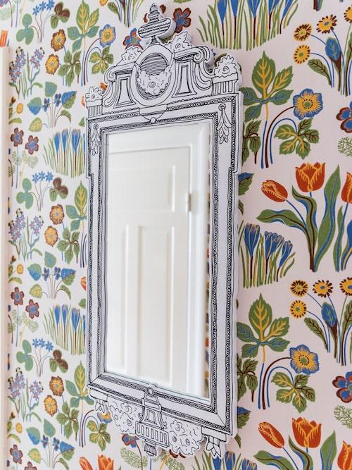 """En lekfull """"gustaviansk"""" spegel i mdf av Eric Ericson blir en spännande kontrast till den blommiga tapeten. Spegel, Svenskt Tenn."""