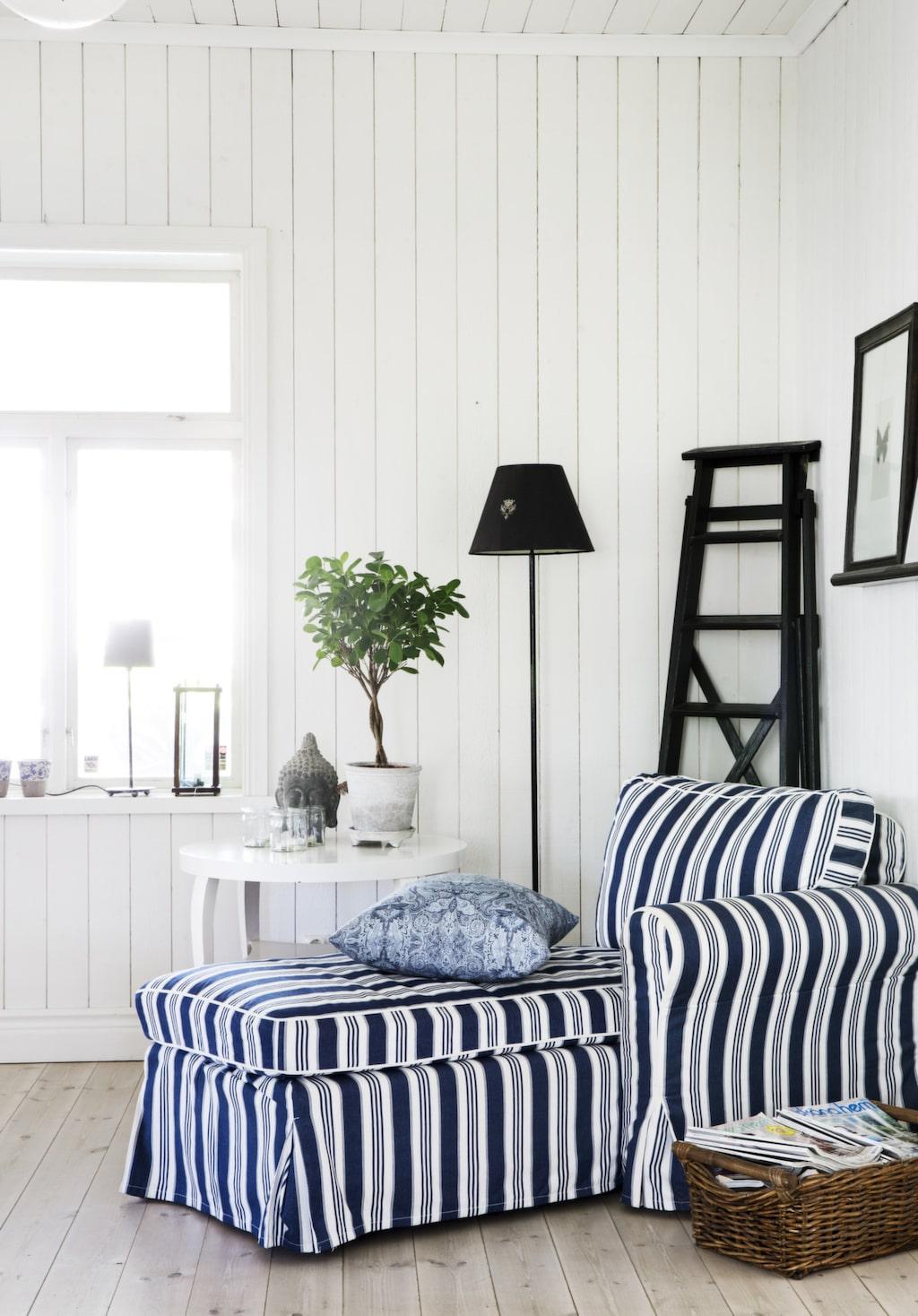 I rummet mellan köket och vardagsrummet står en härlig läsfåtölj från Ikea. Bord och stege är loppisfynd.
