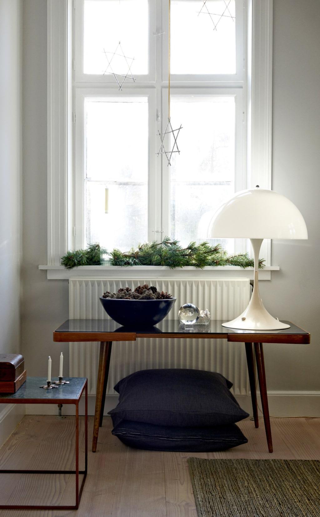 På det antika bordet står en stor skål med kottar och i fönstret ligger tallris. Lampan från Verner Panton är den klassiska Panthella.