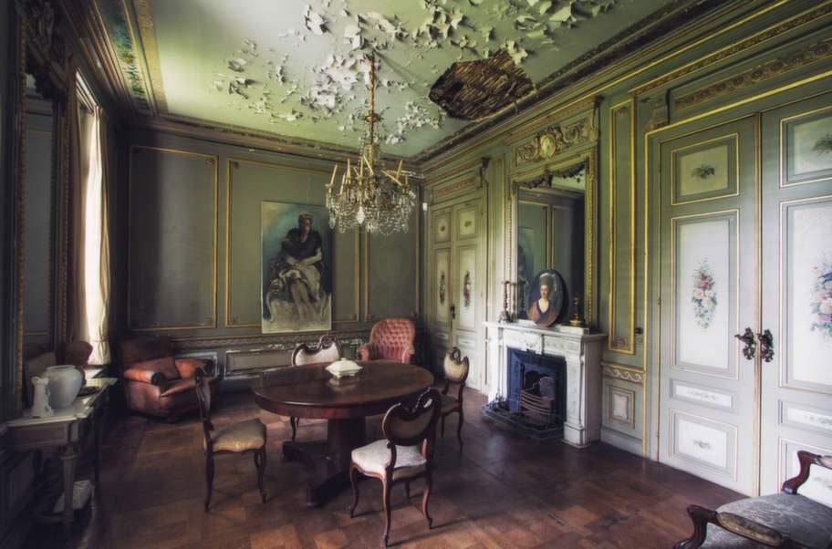 Den vackra, belgiska salongen har påkostad inredning och möbler, men den flagande takfärgen avslöjar att ingen bott här på länge.
