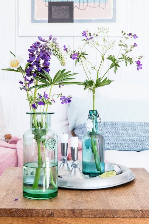 Sommarbuketterna plockas utanför dörren och står i olika flaskor och vaser överallt sommartid. Grön vas, Rum & Trädgård. Turkos flaska och tennljusstakar är loppisfynd. Rosa pläd och linnekudde, Himla. Silverbrickan är en present till familjen.