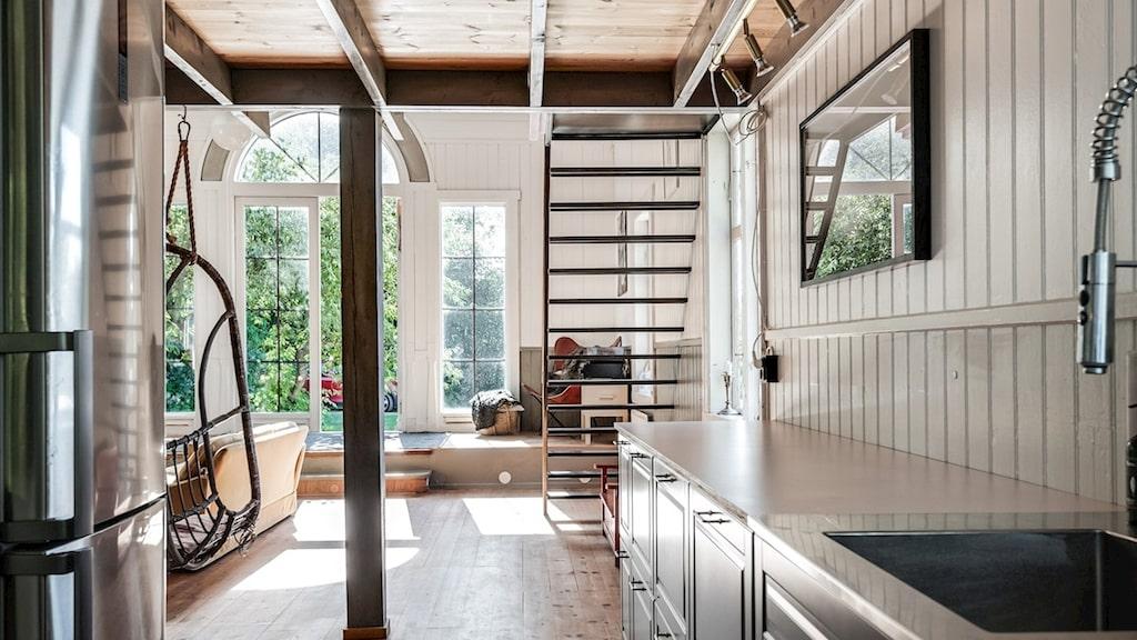 Vy från köket mot salen och trappen upp till läktaren och övervåningen.