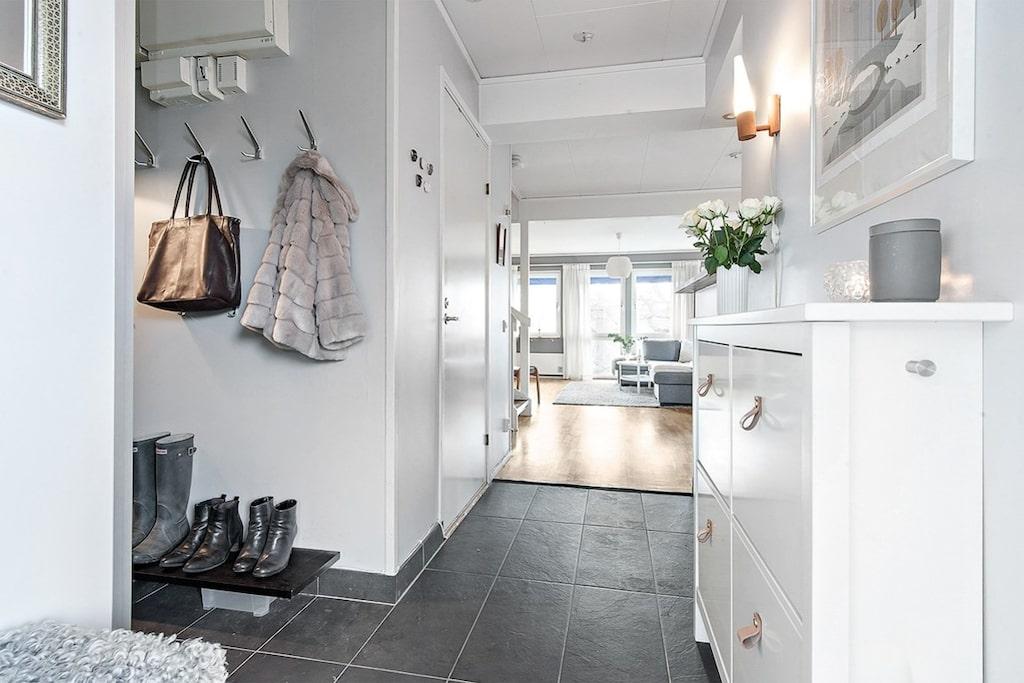 Hallen är rymlig och ljus hall och går i halvöppen planlösning mot det ljusa vardagsrummet och köket. Klinkergolv vid entré och ljusa väggar samt avhängning för ytterkläder.