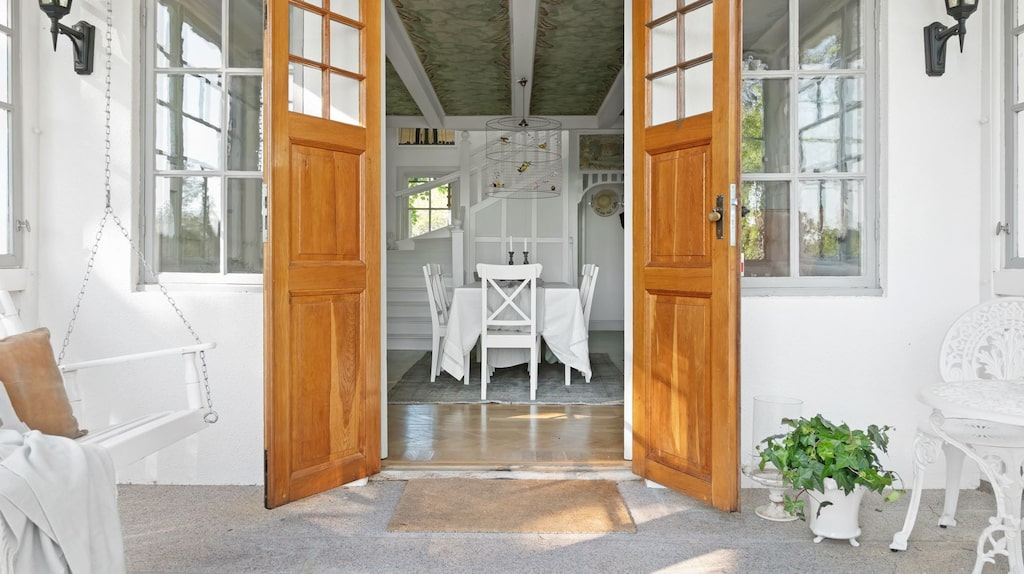 Vy från den inglasade verandan på bottenvåningen, med hall och trapp till övervåningen.