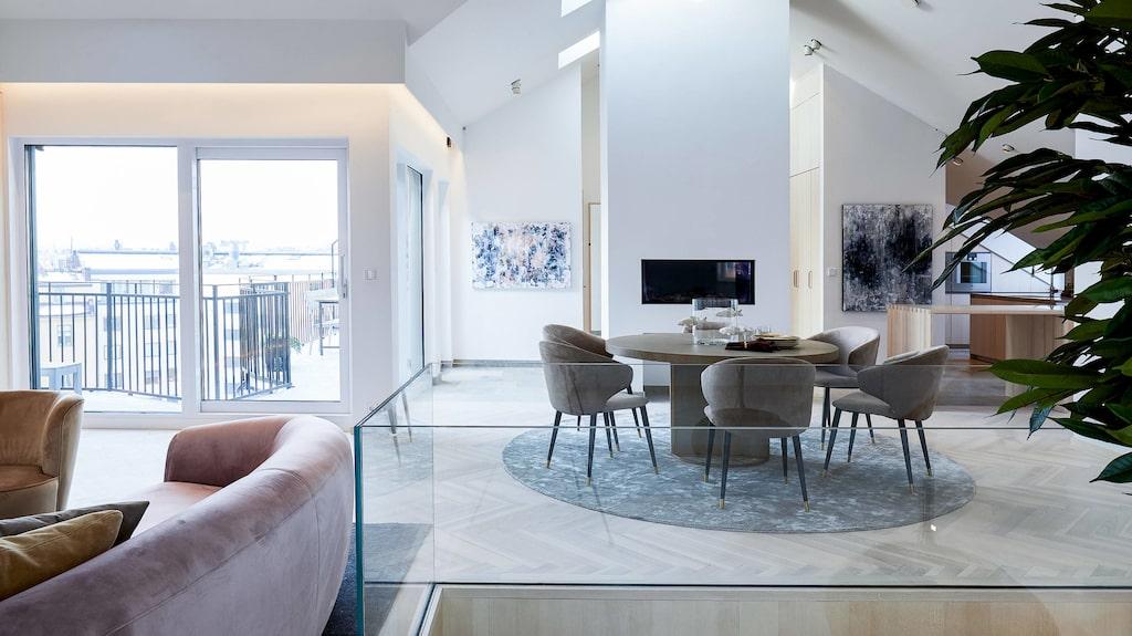 Lägenheten är i två etage. Övre plan är en öppen yta för socialt umgänge med panoramafönster mot terrassen som bjuder på en vacker vy.