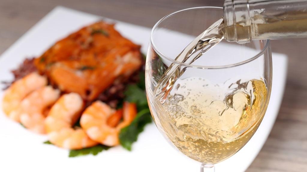 Vitt vin till lax passar ofta fint ihop, men prova även rött till fisken.