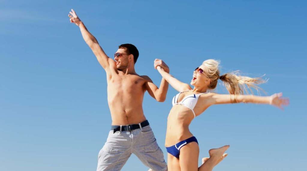 lev dolgachov picture of happy couple jumping on the beach (focus on man).