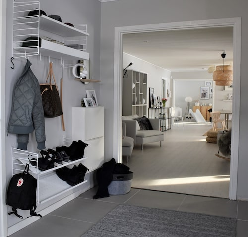 Ordning och reda råder i hallen. Huset har generösa öppningar mellan de olika rummen. Matta, Hemtex. Hyllsystem, String Furniture.