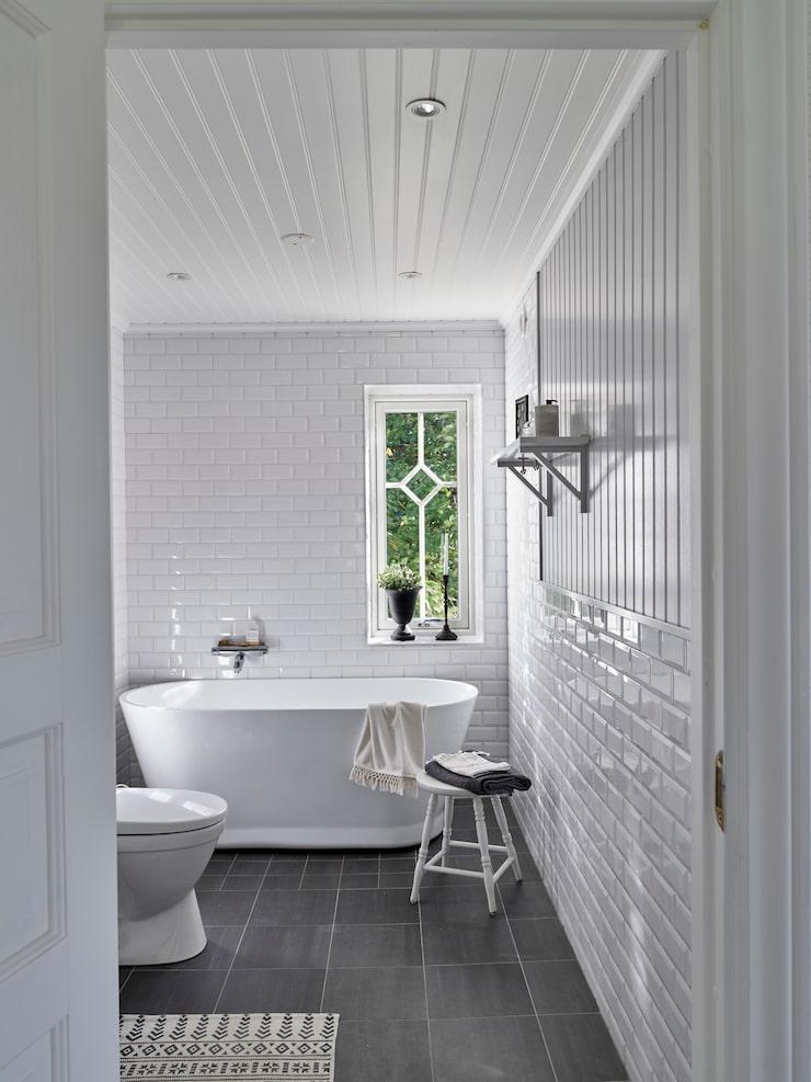 Väggarna i badrummet är klädda med en mix av kakel och pärlspont för att inge en äldre känsla.