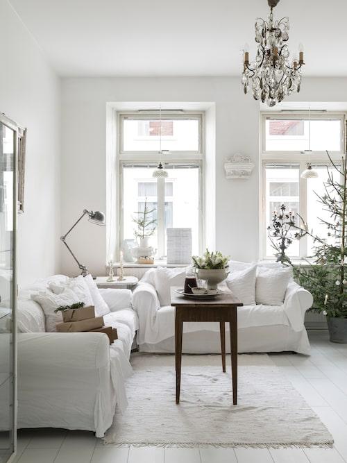 De stora fönstren ger en rofylld känsla i vardagsrummet. Bordslampan är en Jieldé, en fransk industrilampa, köpt i antikaffären Suedeco i Kungälv. Kakelugnsdekoren mellan fönstren är köpt i en antikaffär i Köpenhamn.