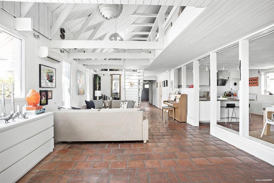 Ett mycket rymligt L-format vardagsrum, med glaspartier mot kök och matsal.