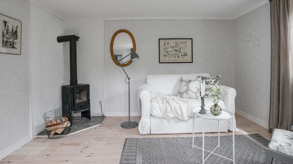 Det vitvaxade plankgolvet återfinns i hela bottenplan. Här allrummet med en liten vedspis, en mindre soffa och två fåtöljer samt bord vilket lätt får plats. Med en bäddsoffa kan man dessutom ha övernattande gäster.