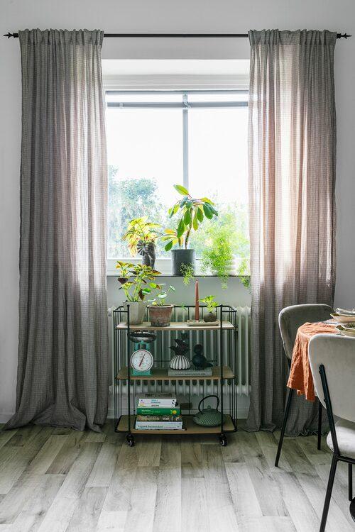 När Myriam tog över lägenheten lades nya golv i alla rum. I köket valde hon ett laminatgolv i grått. Serveringsvagnen kommer från Dorre (Royal Design), gardinerna som bidrar med både en ombonad känsla och en mjuk spridning av ljuset kommer från Jotex. Stolar, Ellos.