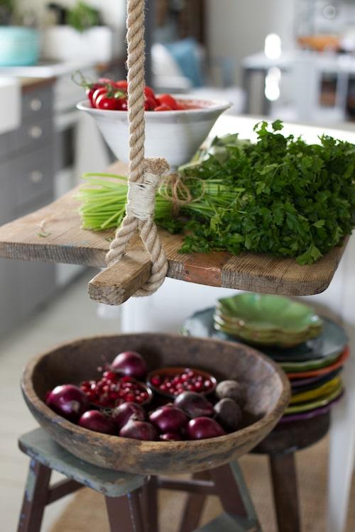 """En krok i taket och ett rep håller upp den vikbara """"köksön"""" när den inte behövs. En skärbräda har monterats med gångjärn på den befintliga lilla köksön för att utöka arbetsytan. Keramiken är skapad av Åsas mamma Helena Barrsjö."""