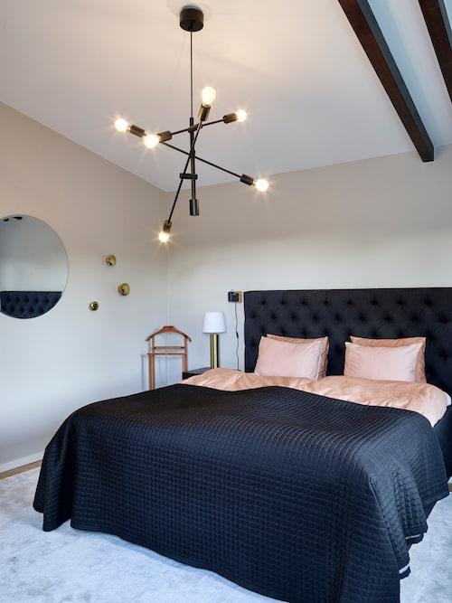 Linnea och Anderas sovrum som är inrett i sober hotellstil ligger på övervåningen under snedtaket. Säng, Carpediem. Sängkläder, Hästens. Spegel och taklampa, Gekås. Sänglampor, H&M Home.