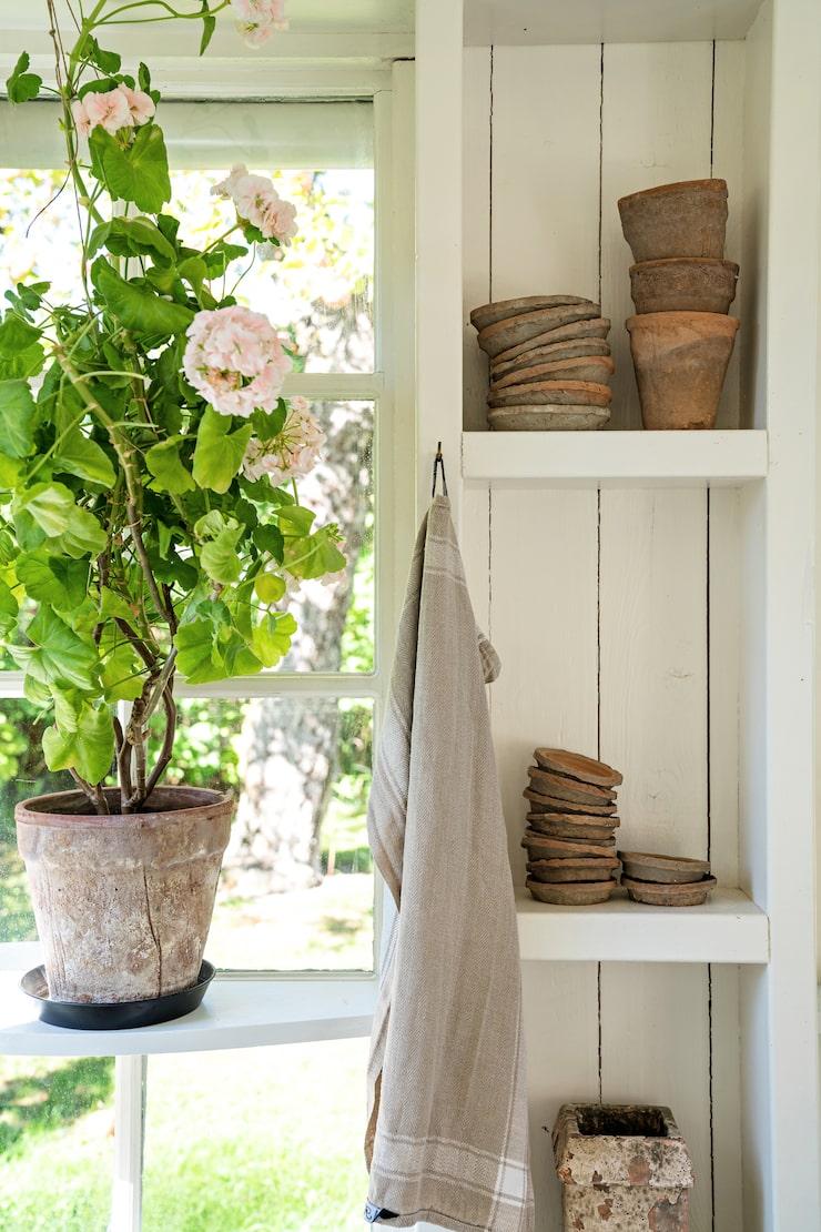 Hyllorna mellan fönstren blev en naturlig lösning av regelverket när lusthuset byggdes. Här förvaras krukor och vaser som vackra stilleben tills det är dags att använda dem igen.
