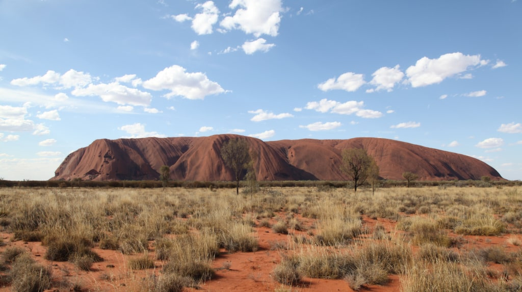 Ayers rock sticker upp som en ö i det torra landskapet.