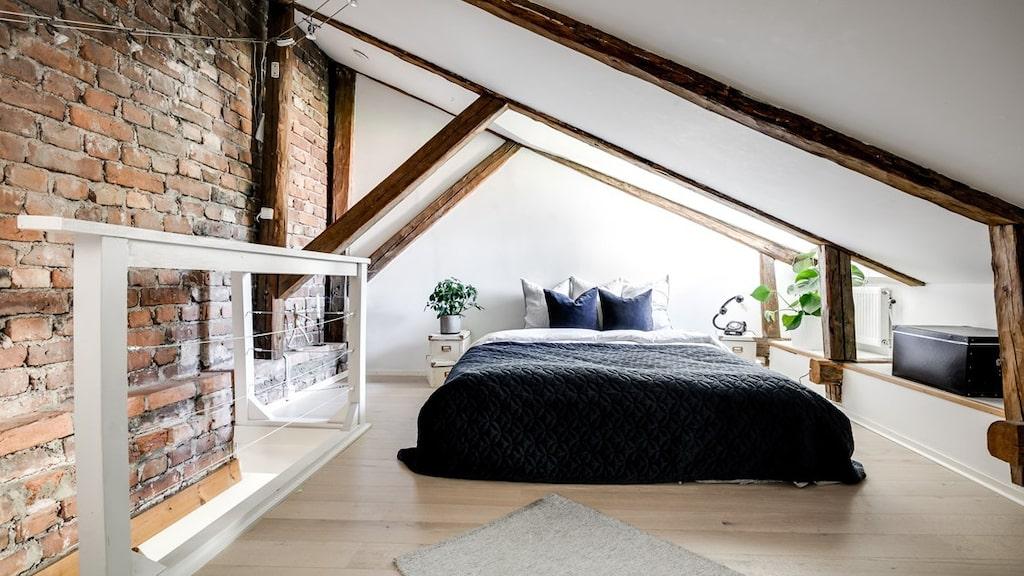 Sovloftet med snedtak och takbjälkar rymmer en dubbelsäng. Härifrån har man utsikt mot Gustav Vasa kyrka.
