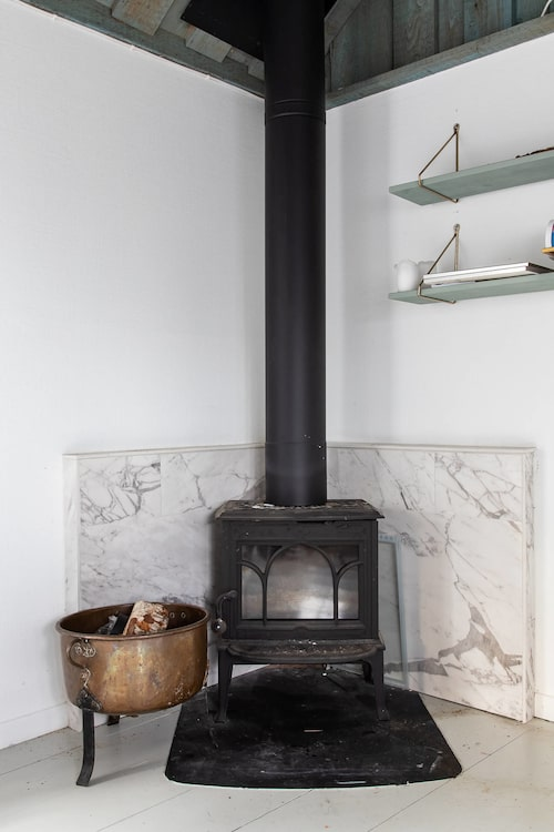 I vardagsrummet kan man värma sig framför braskaminen.