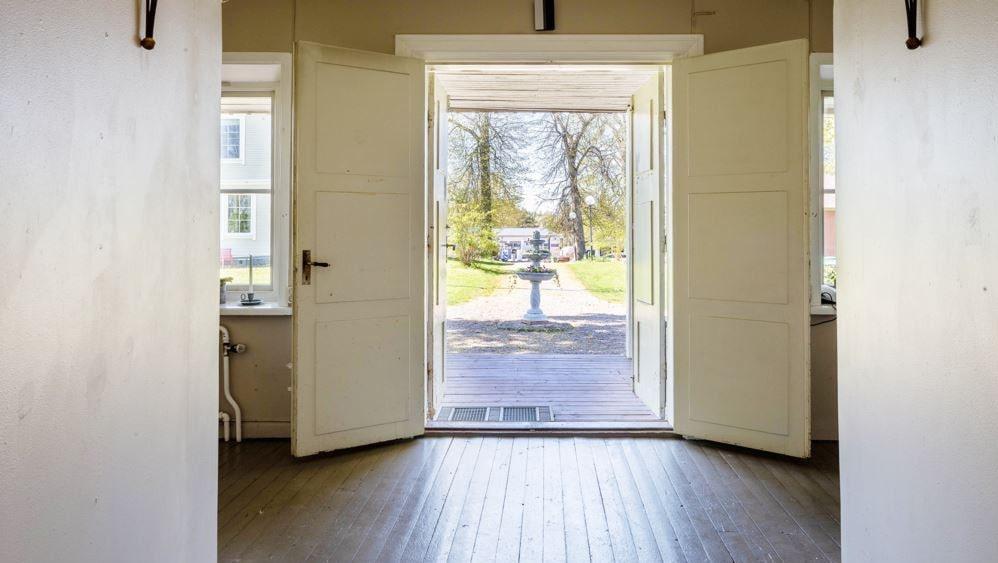 Härlig vy från hallen och entrén ut mot tomten. Man ser gången upp mot huset och fontänen som står utanför och porlar.