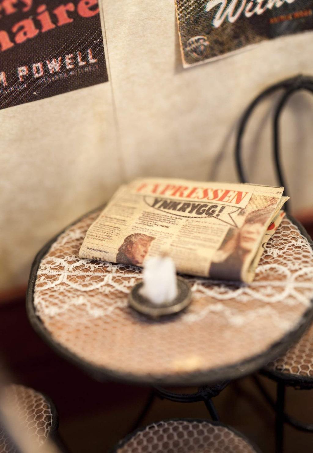 På bordet i kaféet ligger det en Expressen och ett blockljus. Det är tårtljus som Lotta klippt till i flera små delar.