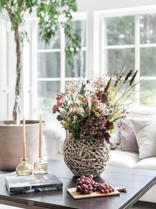 En höstig bukett med blommor från blomsteraffären har blandats upp med blommor från trädgården.