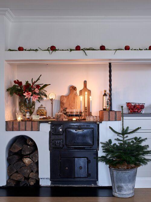 Den gedigna vedspishörnan är pyntad med juläpplen och lummer och fungerar som glöggbord i juletider.