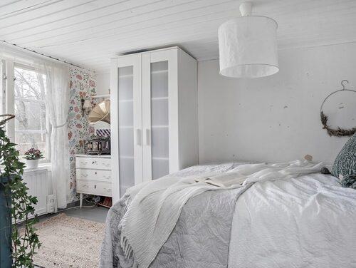 Ljust sovrum. Stugan har mönstrade tapeter och ljus inredning.