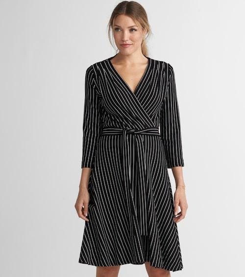 Klänning Celia från Jumperfabriken i feminin modell med djup v-ringning, omlott fram och utställd kjol, 1 500 kr, Ellos.