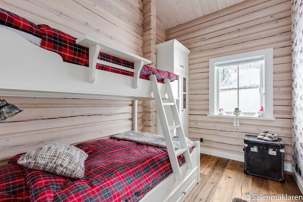 Ett av fem sovrum, här med våningssäng. Ekgolv och vitlaserade timmerväggar. Platsbyggd garderob.