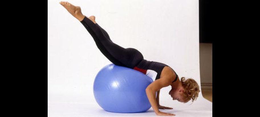 6. Handstående: Lägg dig över bollen så att du har stöd för bröstkorgen. Håll armarna böjda och händerna plant mot golvet. Håll ihop benen och lyft dem mot taket så att du står som i halvvägs handstående. Dra långsamt benen åt sidorna så långt du kan utan att det smärtar och håll ett par sekunder innan du går tillbaka. Benen ska hela tiden vara i luften och kroppen skall hållas spänd. Upprepa rörelsen.
