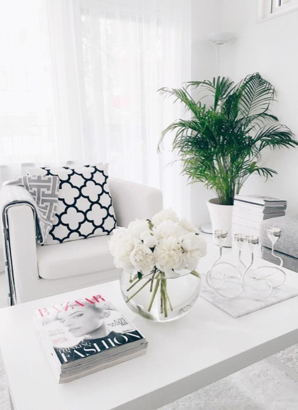 Mysigt. En del av vardagsrummet: Vit fåtölj med kuddar och filt från Elce Stockholm.