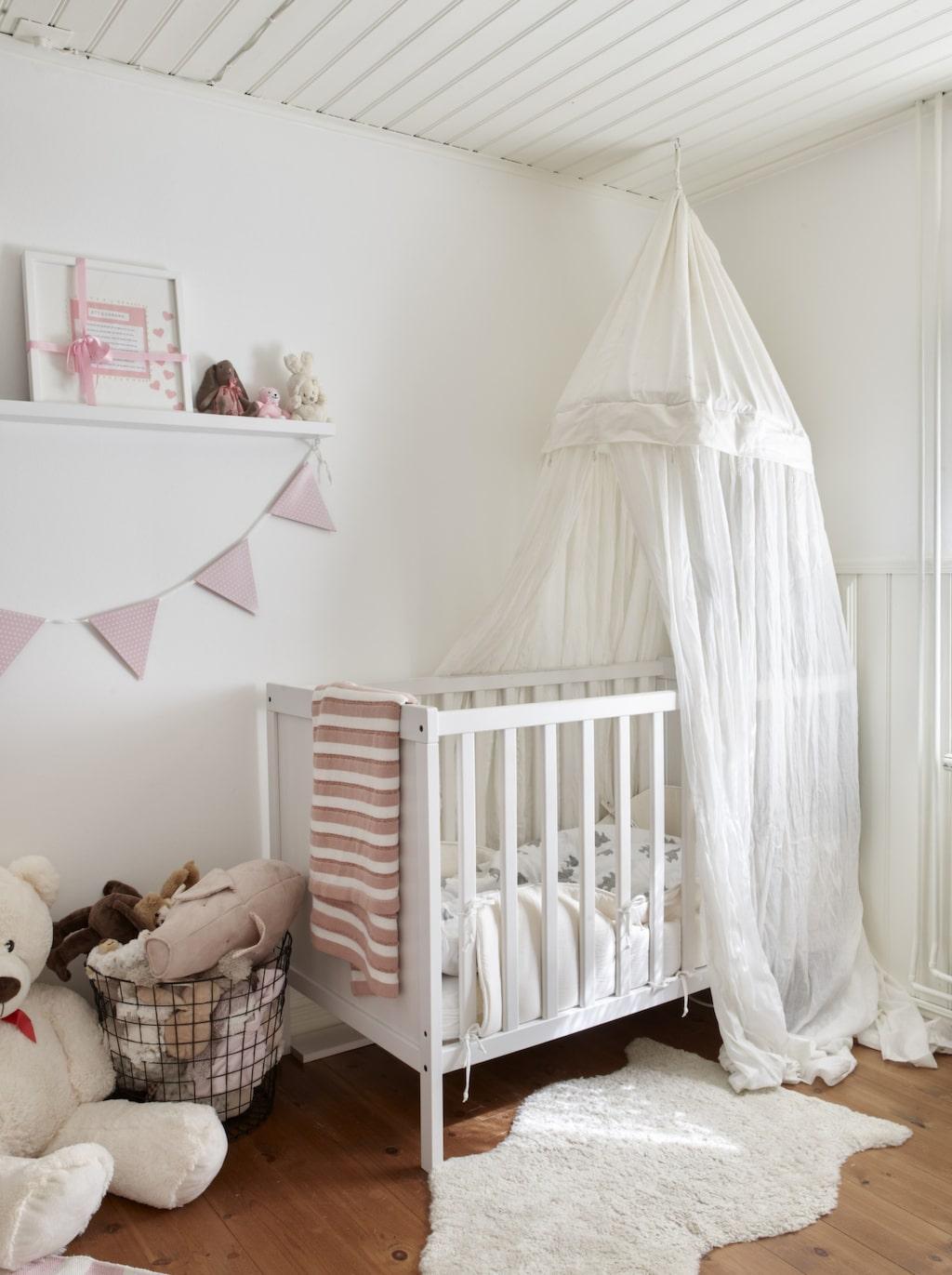 Rosa dröm. Almas rum är litet och mysigt. Spjälsäng från Ikea med sänghimmel från Funky factory. På hyllan samsas doppresenter med mjukisdjur.