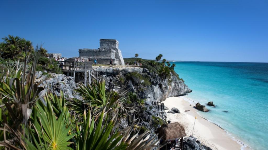 Ruiner vid havet. Ruinerna från Maya-templet i Tulum, ovanför den bländvita stranden och det turkosblå havet.