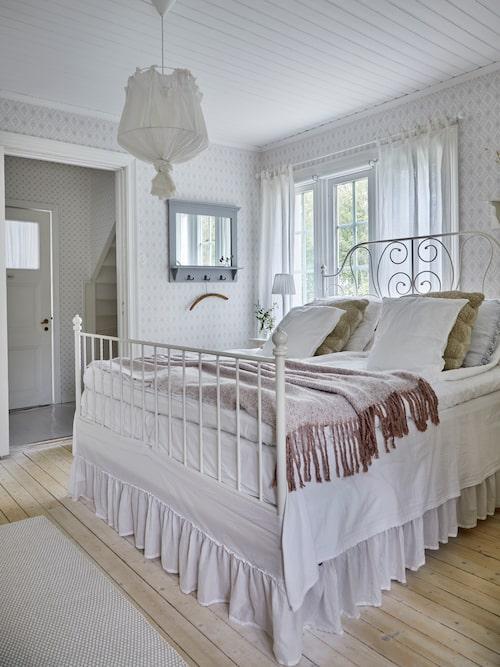 Sofias och Niclas sovrum är inrett i romantisk lantlig stil med den vackra järnsängen placerad vid fönstret.