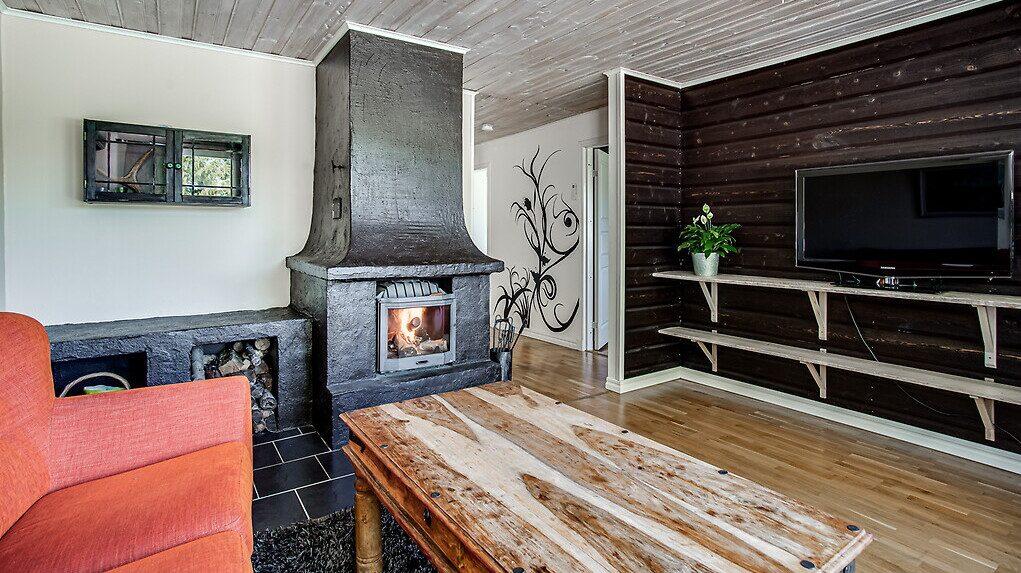 Vardagsrum med parkettgolv samt öppen spis. Här sitter också bostadens luftvärmepump som är installerad 2016.