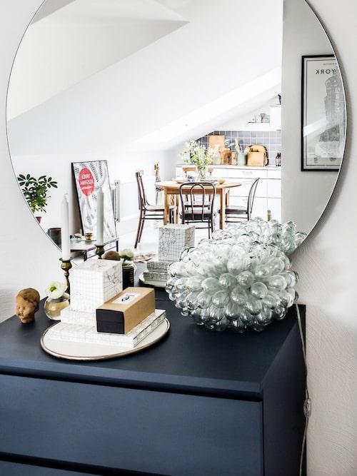Speglar är ett smart sätt att lura ögat och skapa rymd i ett rum. Annas runda spegel kommer från House doctor. På den ommålade byrån Malm från Ikea står lampan Cluster lamp från Artilleriet. Det lilla huvudet av keramik har Anna fått av en god vän.